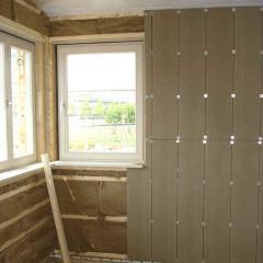 Holzhaus&Lehm - Lehmbauplatte bei der Montage, die Installationebene ist mit Holzfasern gedämmt